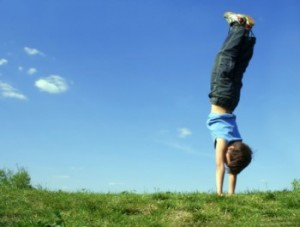 child doing handstand outside