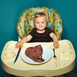 baby eating steak in high chair
